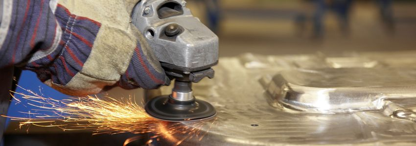 Manufacturing Jobs Birmingham Alabama - worker using angle grinder on metal surface making sparks